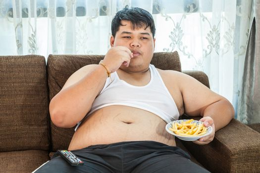 Lazy overweight asian male sitting with fast food on couch and watching television