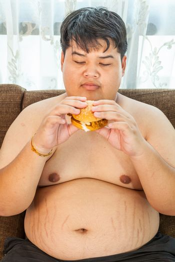 Asian fat man eating hamburger seated on armchair