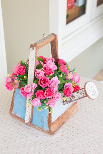 Roses in wood basket on wood table