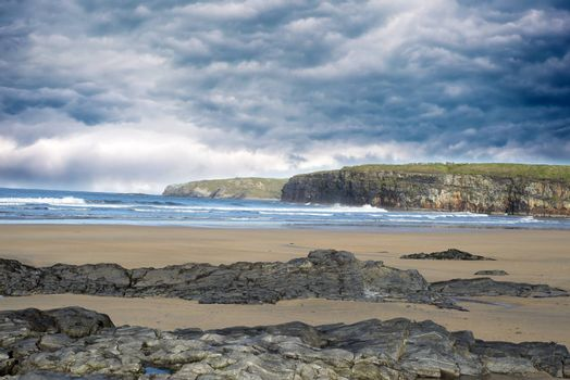 storm clouds with soft waves break on the beach and rocky sand at ballybunion