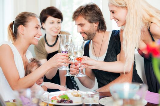 Four young people and a baby are celebrating in restaurant in casual clothing. Focus on glasses