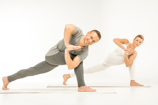 Young couple practicing variation of Revolved Side Angle Pose (Parivrtta Parsvakonasana)