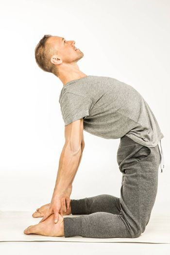 Man practicing yoga standing in Ushtrasana position or Camel pose