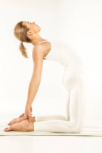 Woman practicing yoga standing in Ushtrasana position or Camel pose