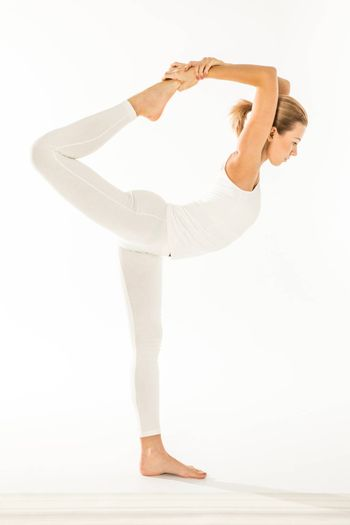 Woman practicing yoga standing in Natarajasana, Lord of the Dance posture