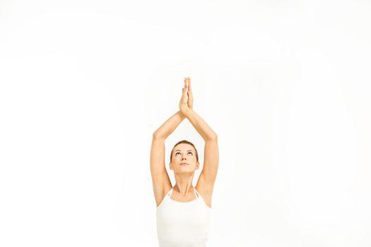 Woman practicing yoga in Easy yoga pose (Sukhasana) with Namaste mudra gesture