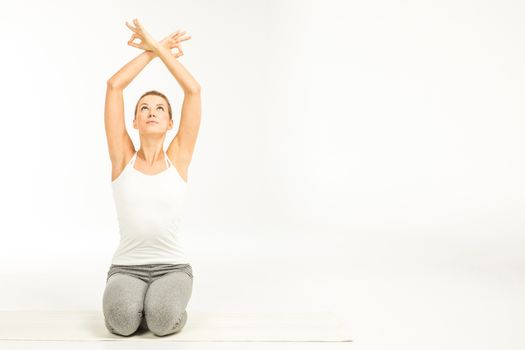 Woman practicing yoga in Easy yoga pose (Sukhasana) with Ohm mudra gesture