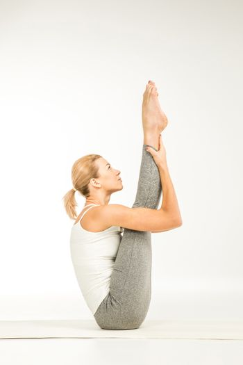 Woman practicing yoga performing boat position on white