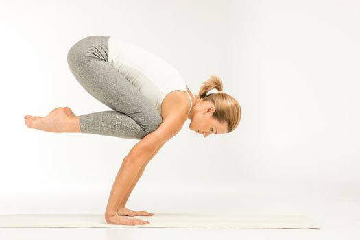 Woman practicing yoga standing in crane pose on yoga mat