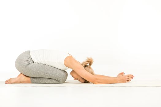 Woman practicing yoga sitting in mudrasana pose on white