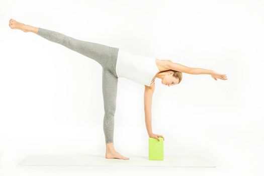 Sportswoman standing on yoga mat and doing Ardha Chandrasana posture, Half Moon Pose with yoga block