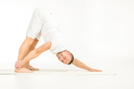 Man practicing yoga and smiling at camera on white