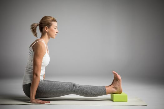 Woman practicing yoga in Angusthasana handstand pose with yoga block