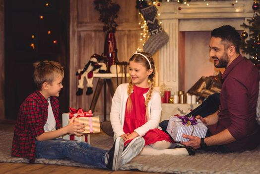 Happy family sitting on floor with christmas presents