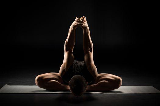 Young man performing Dwikonasana on yoga mat