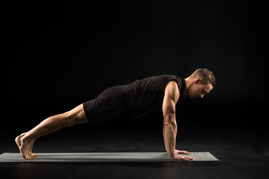 Side view of young man practicing yoga in plank position on yoga mat