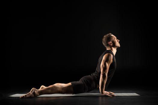 Man practicing yoga performing Urdhva mukha shvanasana pose on yoga mat