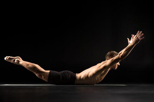 Man performing Salabhasana or Grasshopper Pose on yoga mat