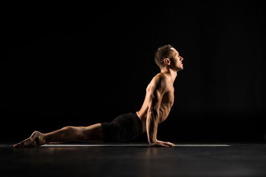 Man performing Bhujangasana ot Cobra Pose on yoga mat