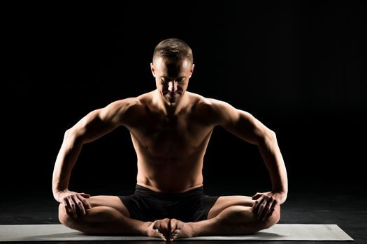Young man performing Sukhasana with closed eyes