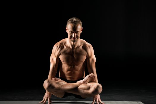 Young athletic man practicing yoga in scale posture on yoga mat