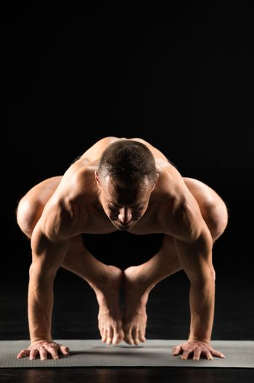 Young athletic man practicing yoga and doing Kakasana or Crow posture on yoga mat