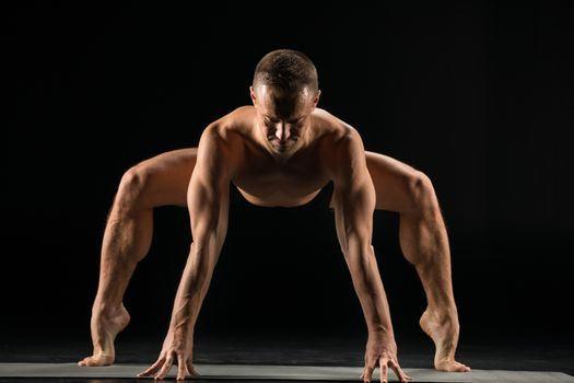Athletic man practicing yoga doing Sumo Squat Pose on yoga mat