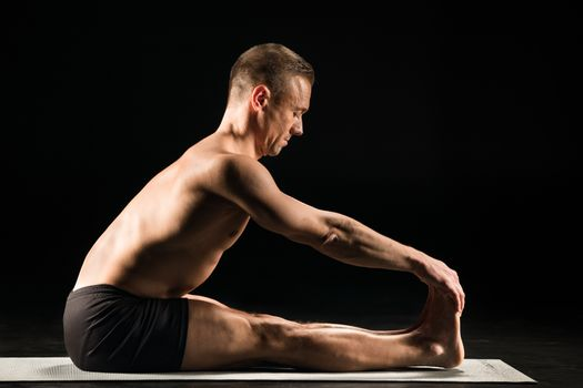 Man practicing yoga while sitting with straight legs and holding toes with hands