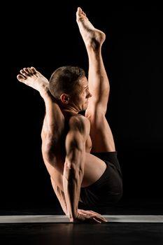 Athletic man practicing yoga doing Astavakrasana pose on yoga mat