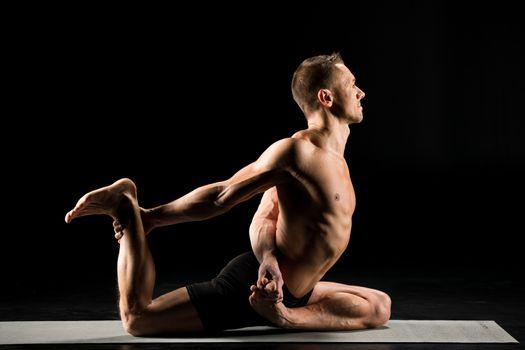 Young man practicing yoga performing pigeon pose variation on yoga mat