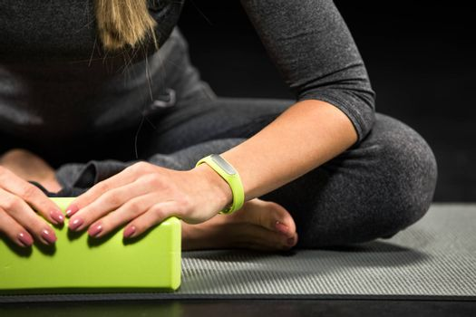 Close-up partial view of sportswoman exercising with yoga block