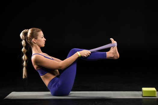 Woman practicing yoga performing boat position with yoga strap