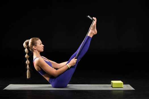 Young woman performing yoga boat position and taking selfie