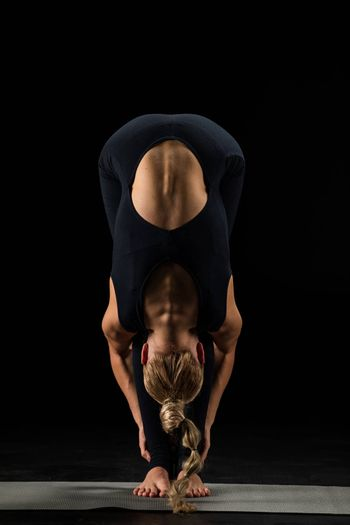 Woman practicing yoga performing Uttanasana or The Standing Forward Bend Pose