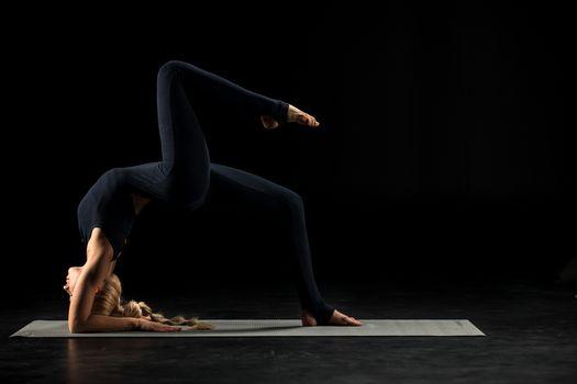 Woman practicing yoga performing Bridge pose on yoga mat