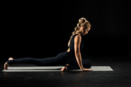 Woman practicing yoga sitting in pigeon pose on yoga mat