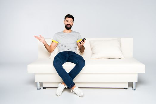 Bearded man sitting on white couch and using smartphone
