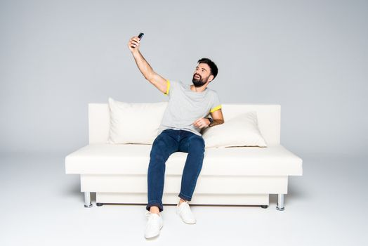 Bearded man sitting on white couch and taking selfie