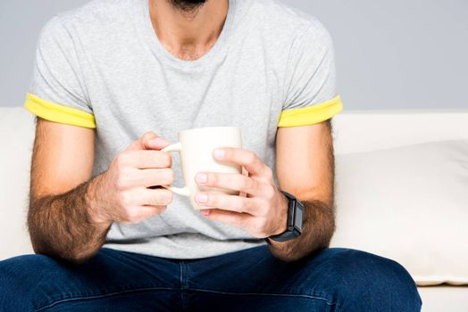 Partial view of man sitting on couch and holding white cup