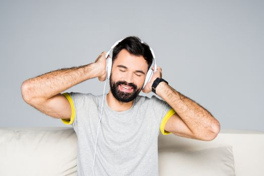 Portrait of bearded man in white headphones listening music with closed eyes