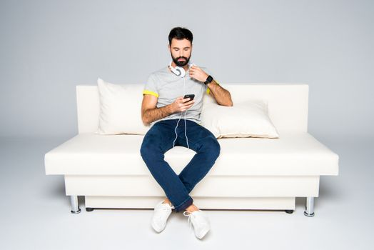 Bearded man in white headphones sitting on couch and using smartphone