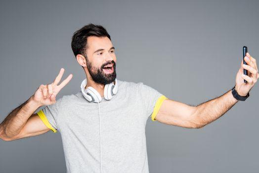 Smiling bearded man taking selfie on grey