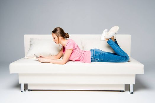 Smiling young woman lying on white couch and using smartphone