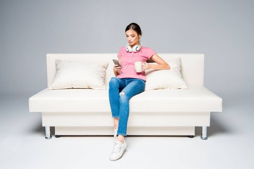 Smiling woman sitting on white couch and using smartphone while drinking coffee