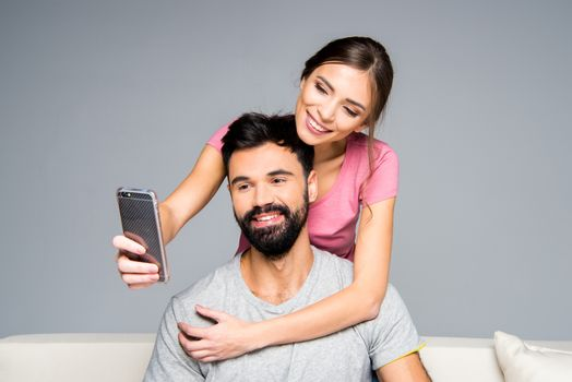 Happy couple taking selfie while hugging on white couch