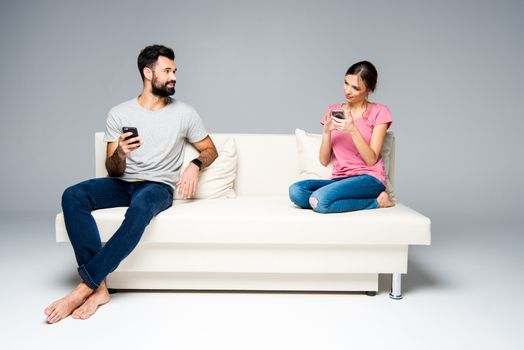 Smiling couple sitting on white couch and using smartphones