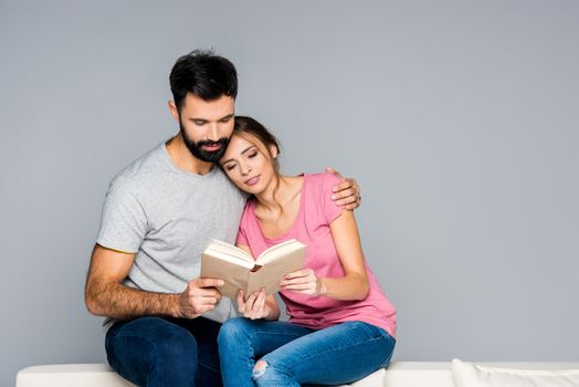 Young couple sitting on white couch and reading book