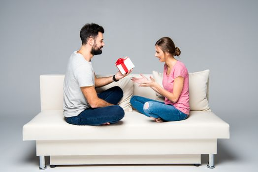 Man giving gift box to happy woman while sitting on white couch