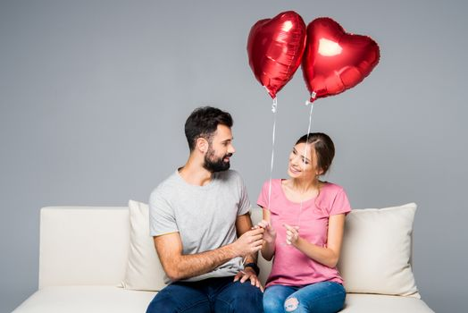 Smiling couple sitting on white couch with red heart-shaped balloons