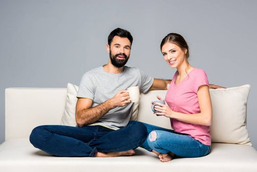 Smiling couple sitting on couch and holding cups